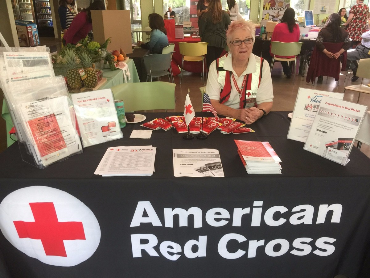 A Red Cross volunteer at an information table.